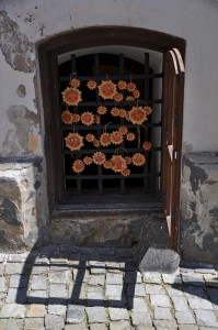 Zamrežované pivničné okno starobylého domu s povešanými keramickými slniečkami.